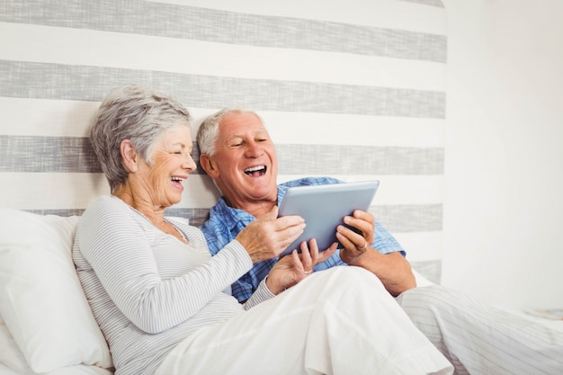 Senior couple laughing while using digital tablet in bedroom Premium Photo