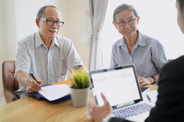 Senior couple listening health insurance by salesman. Premium Photo