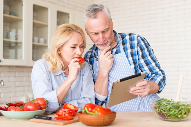 Senior couple looking at digital tablet while preparing the food in the kitchen Free Photo