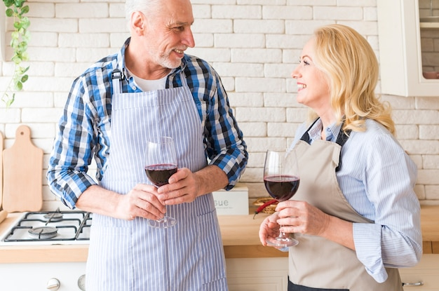 Senior couple looking at each other holding wine glasses in hand standing in the kitchen Free Photo