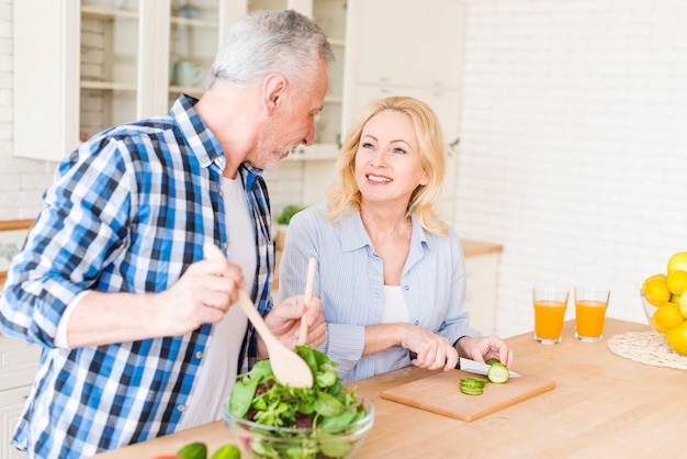 Senior couple looking at each other preparing the food in the kitchen Free Photo