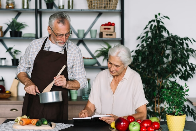 Senior couple looking at recipe in the kitchen Free Photo