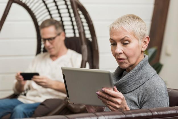 Senior couple looking through their devices Free Photo