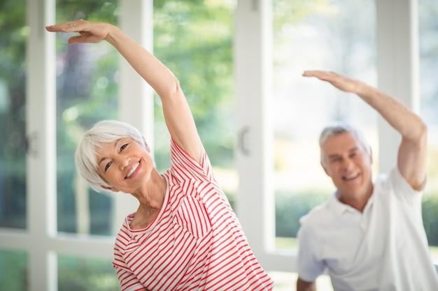 Senior couple performing stretching exercise at home Premium Photo