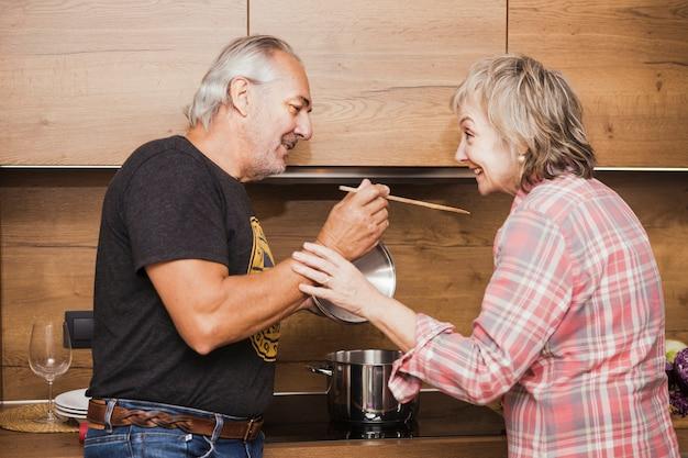 Senior couple preparing dinner in kitchen Free Photo