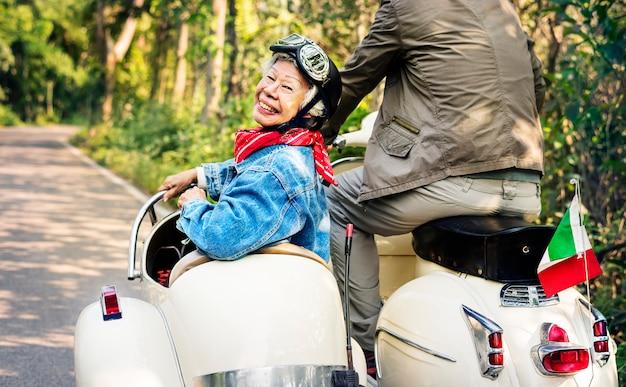 Senior couple riding a classic scooter Premium Photo