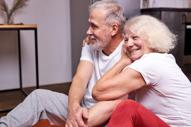 一緒にスポーツ運動をした後、年配のカップルが床で休んで座って、健康でスポーティーであることを楽しんで、笑顔を抱き締めます Premium写真
