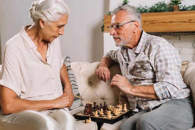 Senior couple sitting on sofa playing chess Free Photo