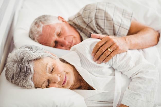 Senior couple sleeping on bed in bedroom Premium Photo