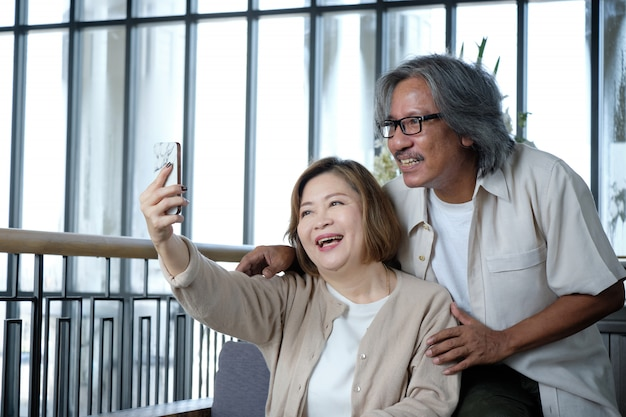 Senior couple taking pictures of selfies, look happiness and warm on vacation. Premium Photo