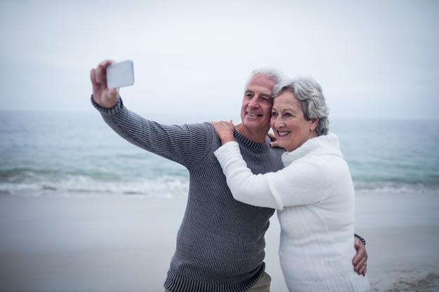 Senior couple taking a selfie on the beach Premium Photo