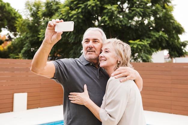 Senior couple taking selfie in garden Free Photo