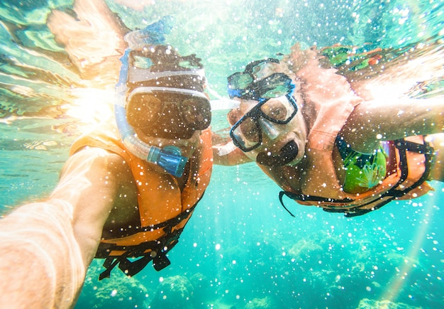 Senior couple taking underwater selfie snorkeling in tropical sea excursion with water camera Premium Photo