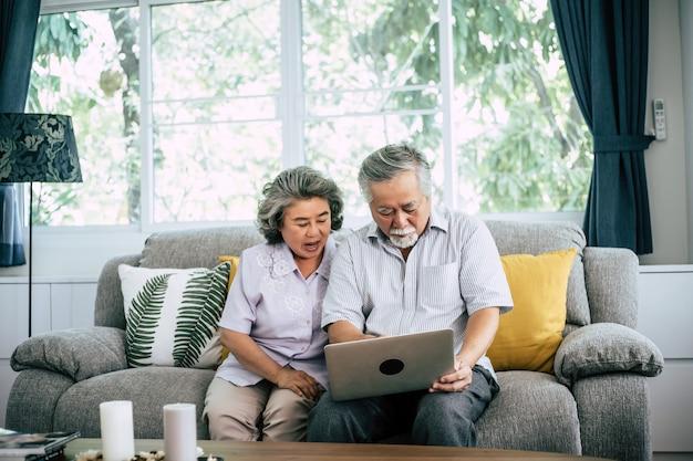 Senior couple talking with laptop computer Free Photo
