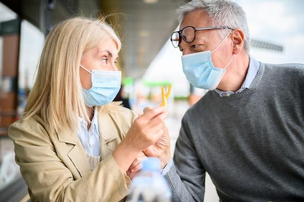 Пожилые супружеские пары жарят картофель фри в фаст-фуде и в масках Premium Фотографии