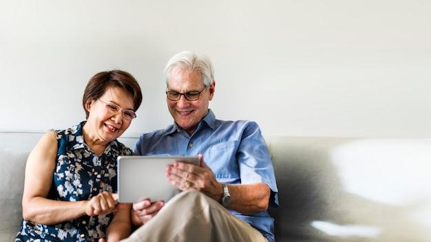 거실에서 디지털 장치를 사용하는 노인 부부 무료 사진