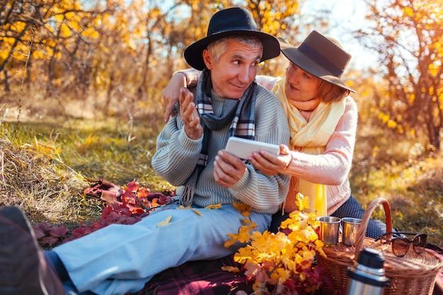 Senior couple using phone while having tea and talking in autumn forest Premium Photo