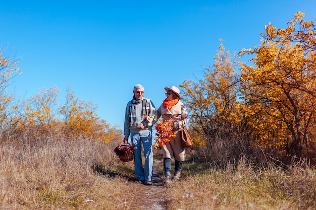 Senior couple walking in autumn forest middle aged man and woman chilling outdoors Premium Photo