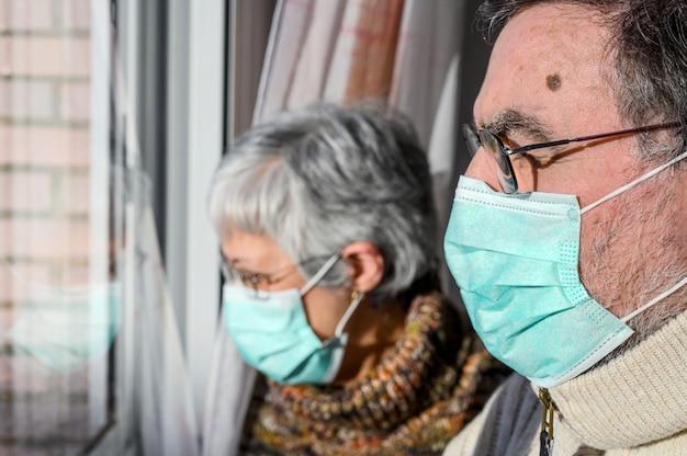 Пожилые супружеские пары, с защитными масками, дома смотрят в окно. концепция коронавируса карантина дома и социального дистанцирования. Premium Фотографии
