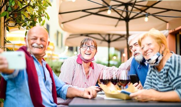 Старшие пары, делающие селфи в баре ресторана с масками для лица Premium Фотографии