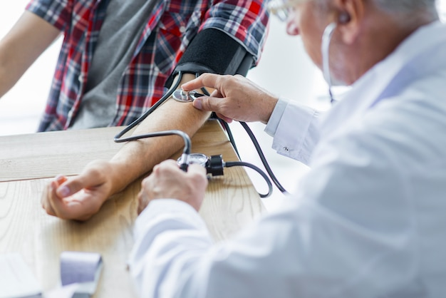 Senior doctor measuring blood pressure Free Photo