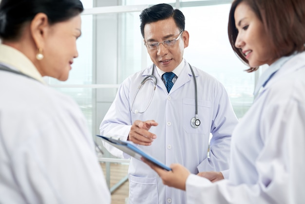 Senior doctors helping newcomer with diagnosis Free Photo
