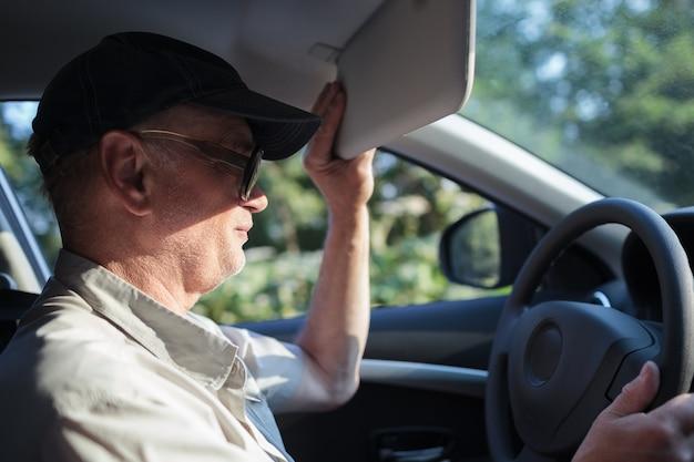 Senior driver hiding from the sun Premium Photo