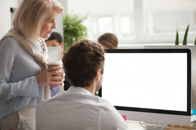 Senior executive checking annual report on computer screen helping colleague Free Photo