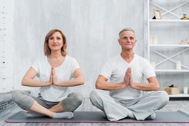 Senior family couple sitting in lotus pose on grey yoga mat Free Photo