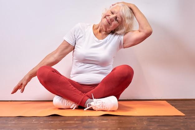 60歳の年配の女性は、運動、レクリエーション、スポーツの概念、幸福に座っています Premium写真