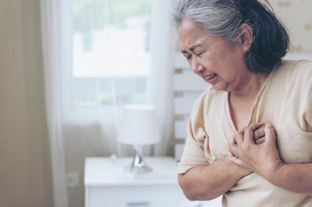 自宅で胸部心臓発作のひどい痛みに苦しんでいるアジアのシニア女性-シニア心臓病 無料写真