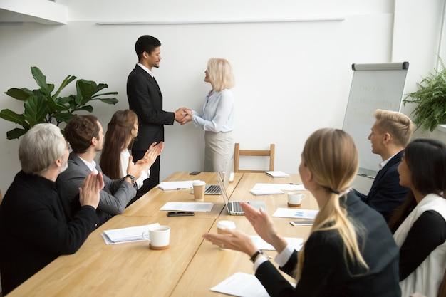 Senior female boss promoting handshaking african employee while team applauding Free Photo
