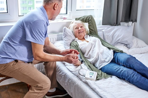 Старшая пациентка в больнице с обеспокоенным мужем, держащим руки, проверяя кровяное давление с помощью тонометра. мужчина помогает, поддерживает Premium Фотографии