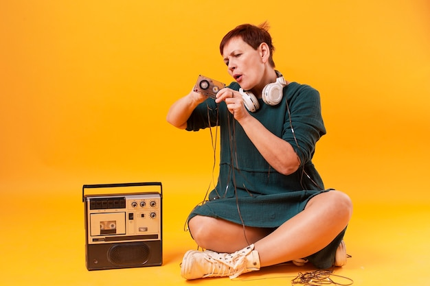 Senior female playing with cassette tape Free Photo
