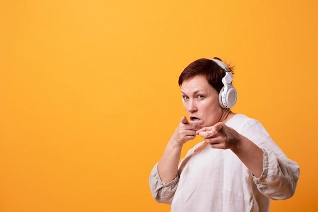 Senior female with headphones pointing Free Photo