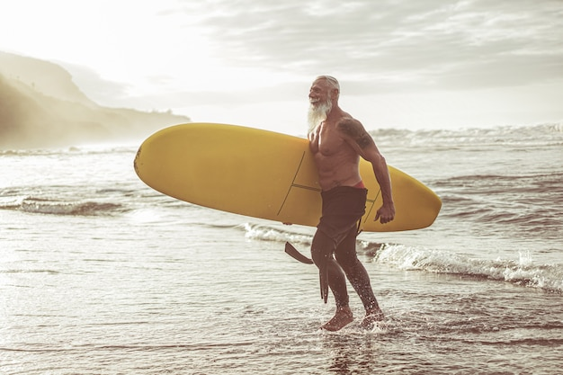 Senior fit guy walking with longboard after surfing at sunset - mature tattooed man having fun doing extreme sport on tropical beach - joyful elderly lifestyle and travel concept - focus on male body Premium Photo