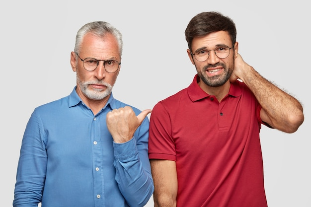 Старший седой молодой мужчина с серьезным выражением лица показывает большим пальцем на своего молодого делового партнера, который нервно смотрит, стоят близко друг к другу, изолированные на белой стене Бесплатные Фотографии