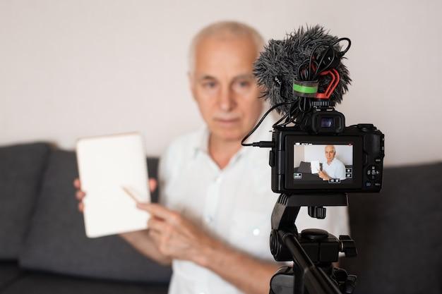 Старший серый слышащий профессор делает видео для лекции дома Premium Фотографии