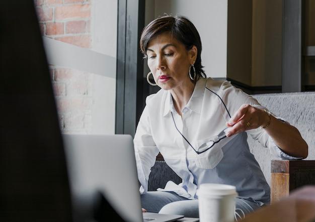 Senior holding eyeglasses in her office Free Photo
