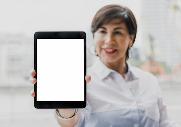 Senior holding a mockup tablet Free Photo