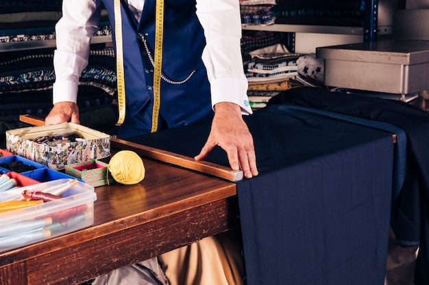 Senior male fashion designer taking measurement of fabric on wooden table Free Photo