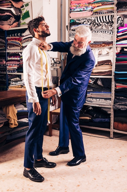 Senior male fashion designer taking measurements of his customer in the shop Free Photo