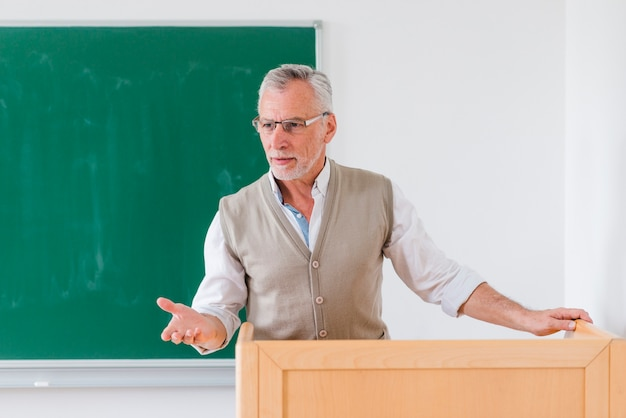Senior male professor explaining lesson near chalkboard Free Photo