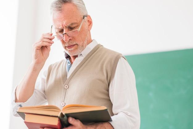 Старший мужчина профессор читает книгу, исправляя очки Бесплатные Фотографии