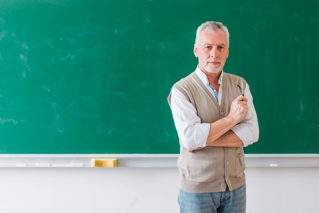 Senior male professor standing against green chalkboard Free Photo