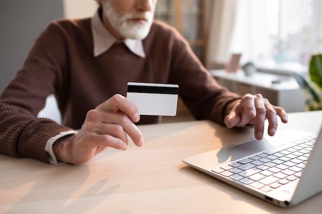 Старший мужчина готов делать покупки в интернете Premium Фотографии