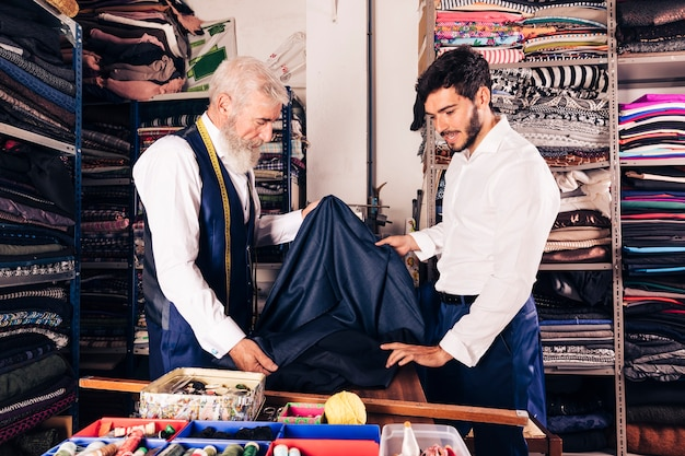 Senior male seller offering fabrics to young man in textile shop Free Photo