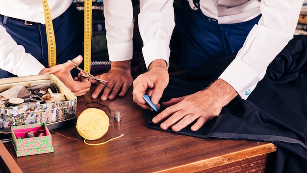 Senior male tailor marking cloth pattern with chalk at workshop Free Photo