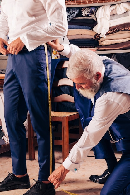 Senior male tailor taking measurement of customer's leg in the shop Free Photo