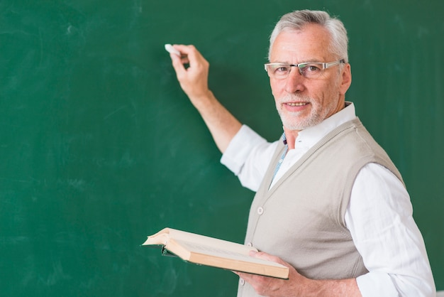 Senior male teacher holding book and writing on blackboard Free Photo